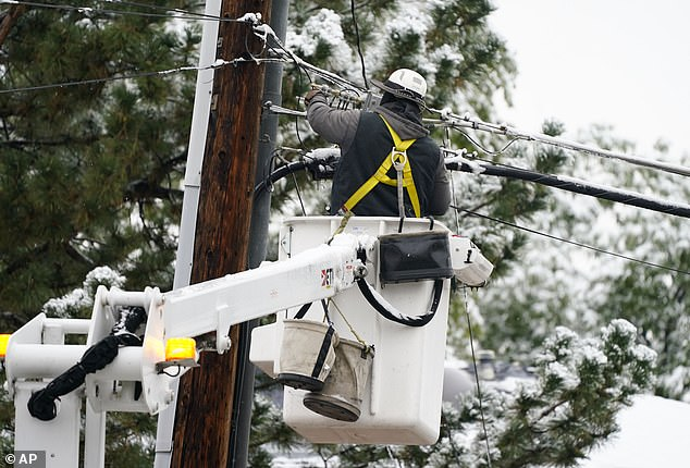 An electrician is seen performing repair work to a power line on Wednesday following a snowstorm in Denver