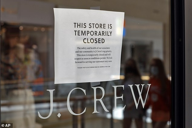 Two shoppers are reflected in the window of the J.Crew store at the International Mall Wednesday, May 6, 2020, in Tampa, Florida. The company filed for bankruptcy this year