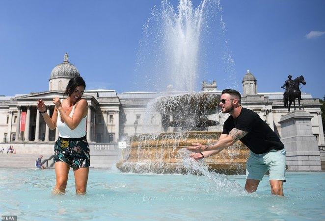Pictured: A couple relax in the sunshine in the fountains at Trafalgar Square in London amid an earlier heatwave in August