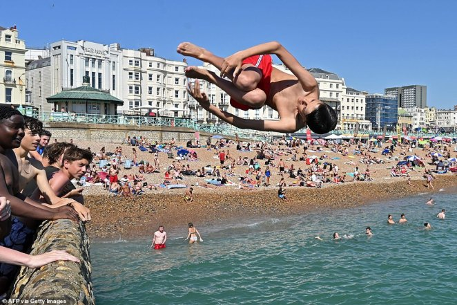 A man jumps from the jetty into the sea in Brighton, on the south coast of England, amid an earlier heatwave on August 7