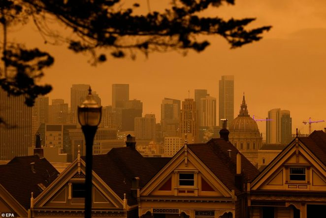 view of the Painted Ladies, the iconic row of historical Victorian homes with a downtown backdrop, under orange overcast sky in the afternoon in San Francisco on Wednesday