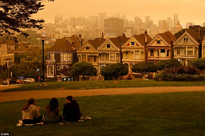 People sit at Alamo Square under an orange and yellow overcast sky overlooking the The Painted Ladies, the iconic row of historical Victorian homes with a downtown backdrop