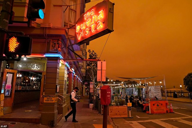 Under darkened skies from wildfire smoke, a waiter carries a tray of Irish Coffee to people having lunch at the Buena Vista Cafe Wednesday in San Francisco. The photo was taken just after midday