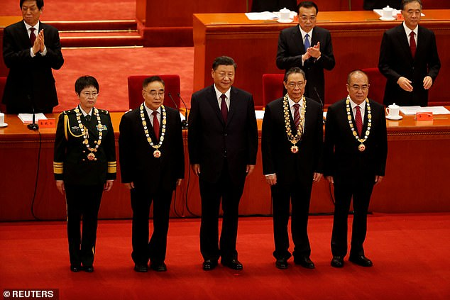 Chinese President Xi Jinping poses with health experts and generals on Tuesday