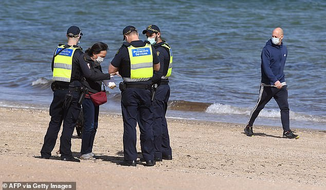 Law enforcement officers speak to a woman on St Kilda beach on September 3. Lockdowns will not be significantly eased until Victoria's new coronavirus cases drop to single digits