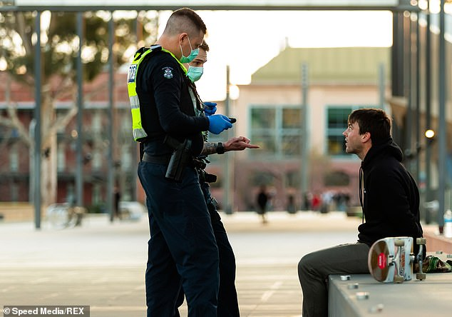 Victoria Police officers speak to a man who was not wearing a face mask in Melbourne. He was allowed to go without being fined and there is no suggestion he did anything wrong