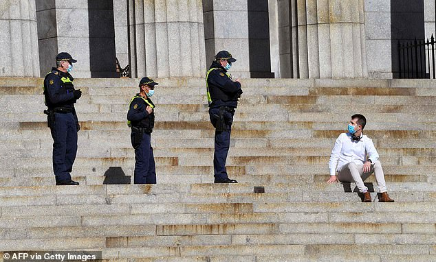 Three armed law enforcement officers are pictured at Melbourne's Shrine of Remembrance approaching a masked man to check his bona fides as he peacefully sits on the steps during the COVID-19 lockdowns