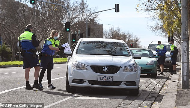 Police are pictured pulling over a driver for a licence and COVID-19 permit check in Melbourne on August 11 on a day 19 deaths were reported
