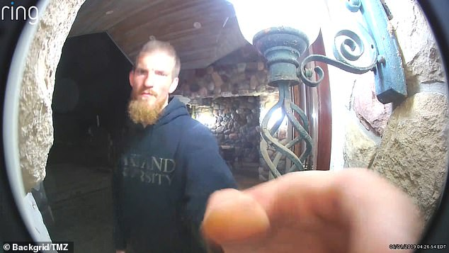 In video footage that was shot in April but released by the court this week Hughes can be seen calmly walking up to the front door of the home before taking a closer peek at the doorcam