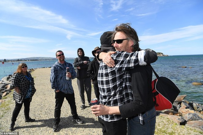 Derek Robinson embraces a family member while holding a bourbon and coke after going missing off the South Australian coast five days ago (left hand)