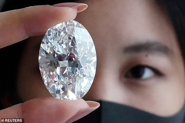 Pictured: An employee of Sotheby's poses with a perfect 100+ carat diamond, the second largest oval diamond of its kind to ever appear at an auction which will be auctioned by Sotheby's in Hong Kong in October