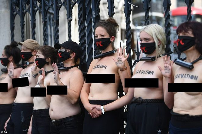 Topless protesters lock themselves to the railings of Parliament during a climate change protest by XR in London