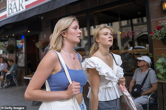 Two Swedish women walk together in Stockholm on August 21 - where businesses have largely operated as normal during the COVID-19 pandemic.
