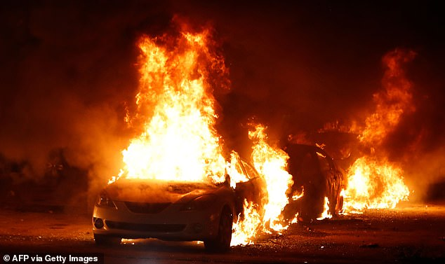 Flames roar from cars torched by protestors a few block from the County Court House during a demonstration against the shooting of Jacob Blake, who was shot in the back multiple times by police the day before, prompting community protests in Kenosha, Wisconsin on August 24, 2020