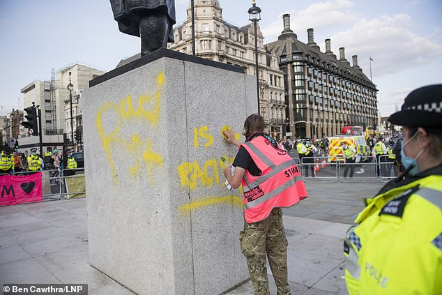 A man tries to clean off the words 'Is a racist' graffitied on to a statue of former British Prime Minster Winston Churchill, outside Parliament, during an Extinction Rebellion demo in London today