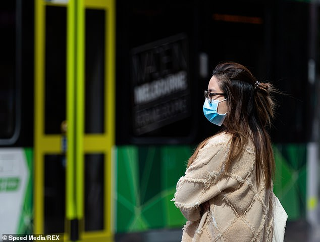 Victoria Police and the health official both said they did not recommend the curfew imposed on Melbourne (a woman wearing a face mask waits for a tram in Melbourne's CBD)
