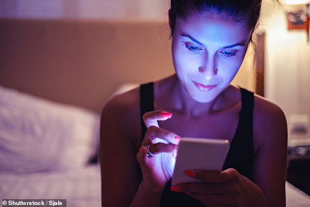 A woman uses a mobile phone emitting a strong blue light. People can reduce skin damage by turning down the brightness of their screens or using 'night mode', which changes the tint from a harsh blue to a soft yellow