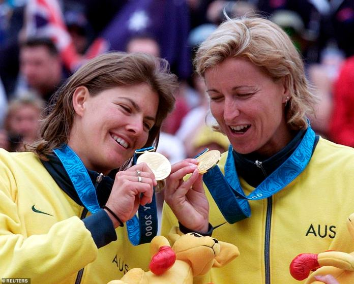 Australians Kerri Pottharst (pictured right)) and Natalie Cook (pictured left) hold their gold medals after winning the final of the beach volley competition at the Sydney 2000 Olympic Games, September 25, 2000