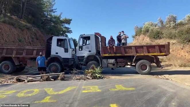 Blockade: Lesbos residents park trucks head-to-head to barricade a road and stop the Moria migrant camp being cleaned up and replaced