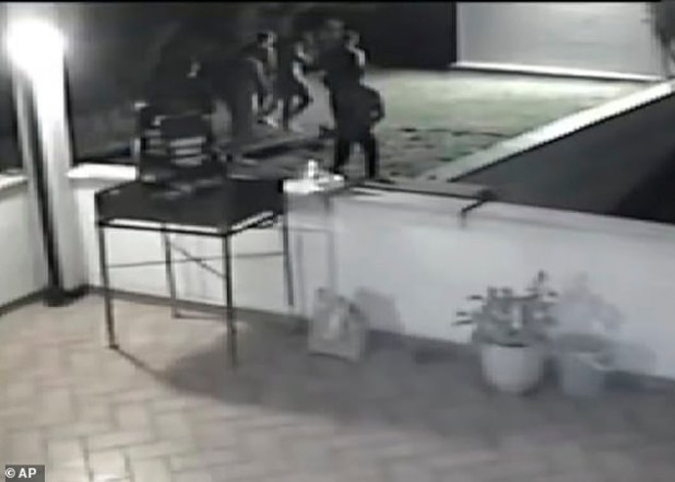 This frame grab, made up of video surveillance released yesterday by Italian police, shows a group of people walking towards the dark corner of a garden in a villa