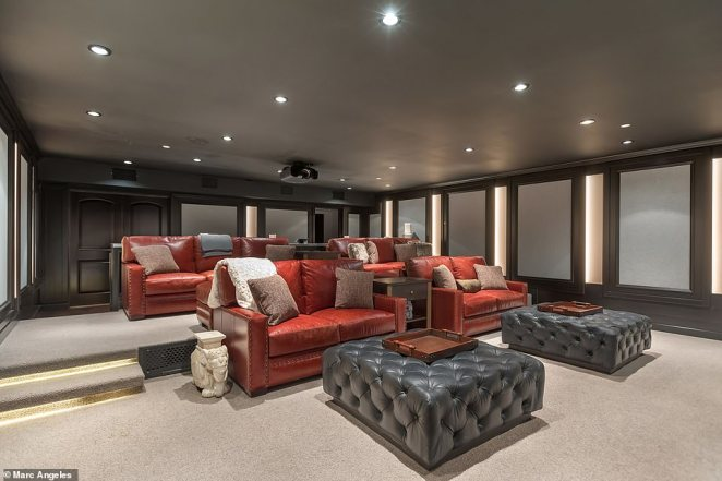 The movie theater in the home offers plush red leather love seats with oversize ottomans and comfy pillows for a perfect movie night with friends or a date night