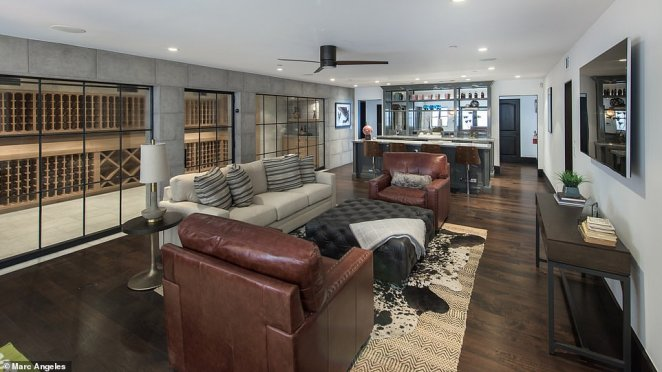 One wall of the wine cellar is full of windows and overlooks a lounging area with a TV mounted on the wall and a bar at one end of the space