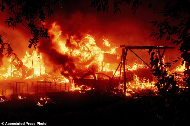BERRY CREEK, CALIFORNIA: Flames consume a home and car as the Bear Fire burns through the Berry Creek area of Butte County, California, on Wednesday