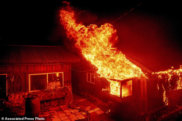 BERRY CREEK, CALIFORNIA: Flames shoot from a window as the Bear Fire burns through the Berry Creek area of Butte County, California, in Wednesday