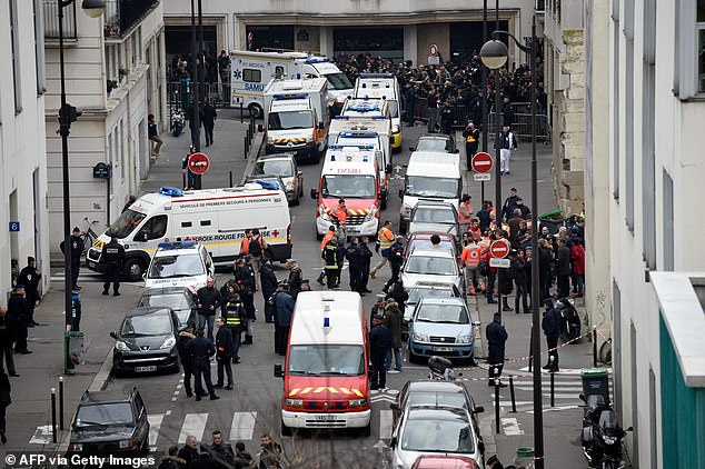 This file photo taken on January 7, 2015 shows a general view of firefighters, police officers and forensic investigators gathered in front of the offices of the French satirical newspaper Charlie Hebdo in Paris, after the brothers Kouachi stormed the offices leaving twelve dead