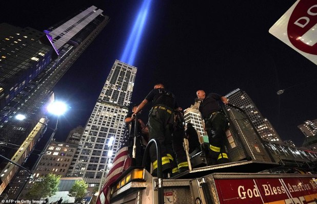 New York Fire Department (FDNY) firefighters stand on their trucks outside the 9/11 Memorial as the Tribute in Light art installation flashes across the sky above Manhattan