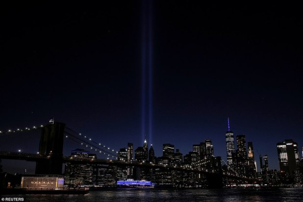 Tributes in the light are seen from Brooklyn as reflections of the Brooklyn Bridge and East River in the foreground