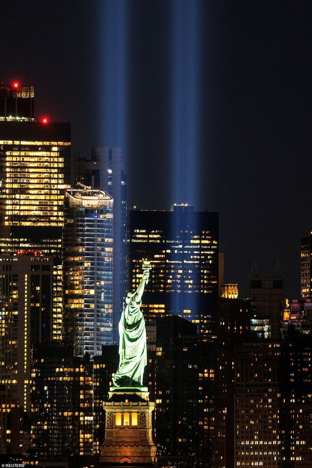 As part of the Lady Liberty tribute, two powerful beams of light have images directly holding their golden torches in the center