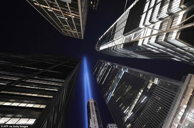 The heist and glass towers of lower Manhattan's financial center are seen, smiling dwarfs ascending in the Tribute of Light.