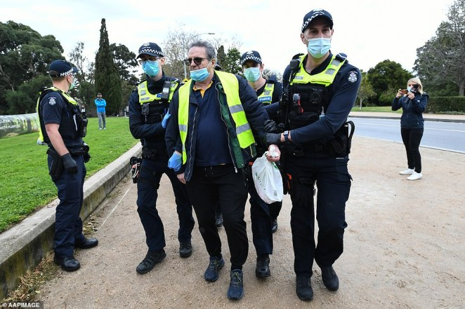 Another man is detained by police at the Freedom Walk protest in Melbourne on Saturday