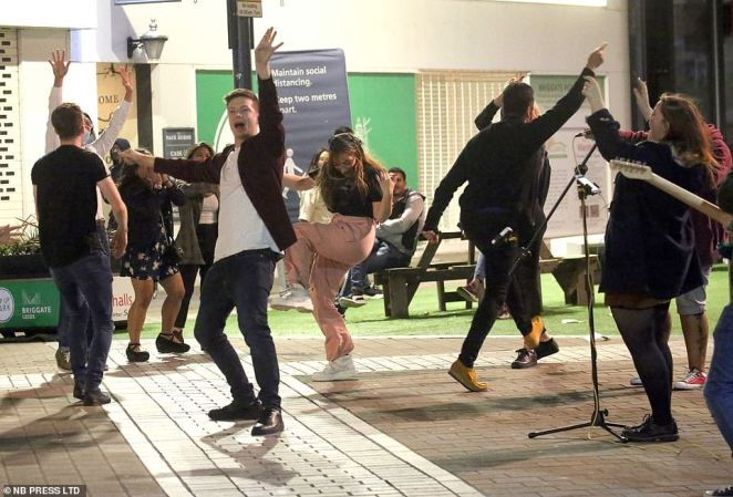 Revellers dance on the street as a band plays in front of shops in Leeds during one of the last big nights out in the city before new rules on groups are introduced on Monday