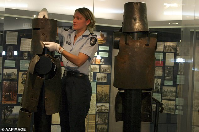 A police officer adjusts the helmet of Dan Kelly's armour which is displayed alongside that of Steve Hart at the Victoria Police Museum. Ned Kelly's armour belongs to the State Library of Victoria and Joe Byrne's is in private hands
