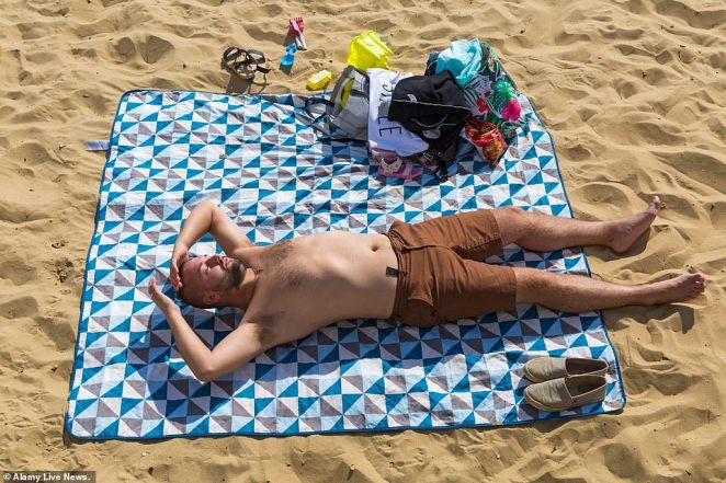 The south of the country (pictured, a man sunbathing in Bournemouth, Dorset, today) will have a largely fine and dry weekend with long spells of autumn sunshine, according to the Met Office