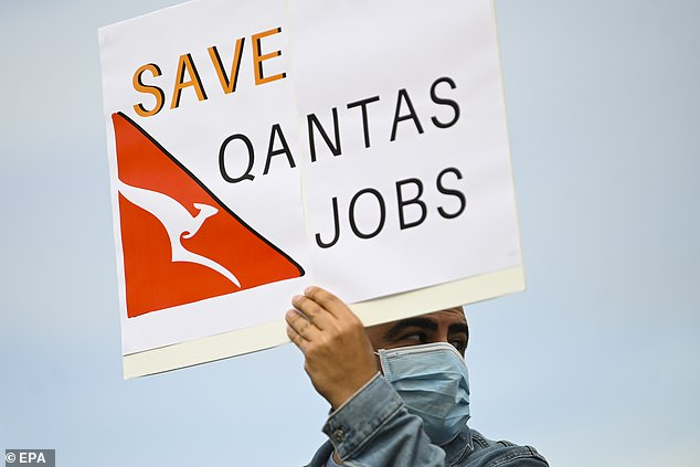 Pictured: A Qantas employee protests outside Parliament House in Canberra earlier this month. Qantas has joined Virgin, Helloworld and Flight Centre to campaign for open borders