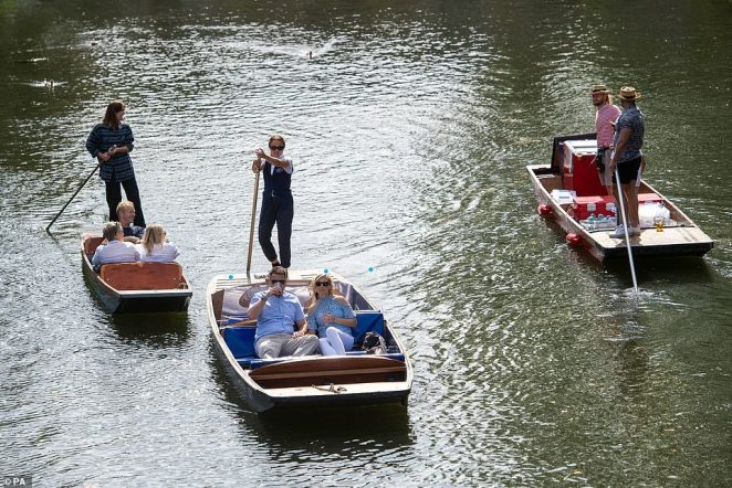 People enjoy a punt trip along the River Cam in Cambridge as three punters work through the warm weather to shunt them across the water