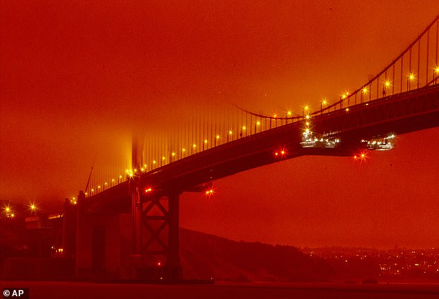 In this photo provided by Frederic Larson, the Golden Gate Bridge is seen at 11 a.m. PT amid a smoky, orange hue caused by the ongoing wildfires, Wednesday