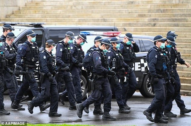Victorian police officers swarm the streets of Melbourne on Saturday. Some officers were on horseback or in riot gear