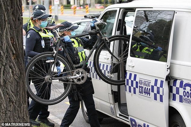 Police carry a bicycle into the paddywagon after arresting a cyclist during the marches