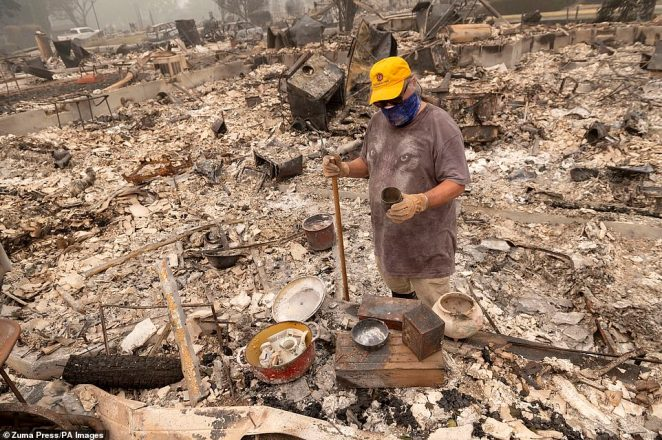 Mark Mousseaux sorts through the burned remains of his house in a neighborhood burned by the Almeda fire in the town of Phoenix in southern Oregon on Saturday