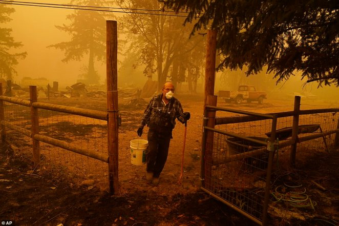 George Coble carries a bucket of water to put out a tree still smoldering on his property destroyed by a wildfire in Mill City, Oregon, on Saturday