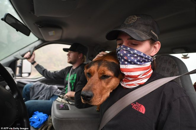 James Smith hugs his dog Rose after returning to his evacuated home to find looters had stolen his motorcycles in Estacada, Oregon, on Saturday.