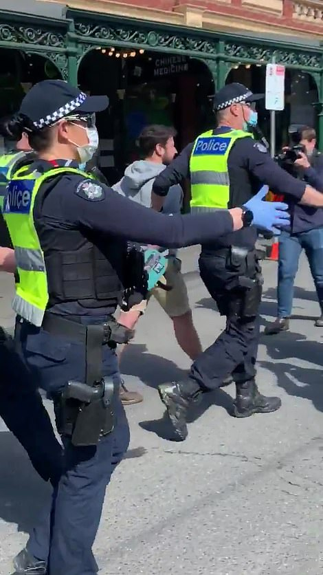 A demonstrator is taken away by police in handcuffs on Sunday