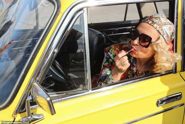 Ladas were first manufactured in 1970s and are one of the Russia's most well-known cars. Pictured: a blond woman reapplies gloss behind the wheel of her yellow Lada