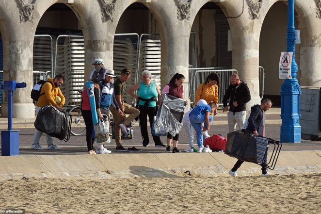 Revellers arrived to Bournemouth beach with their beach gear as temperatures in the UK rise to 77F following a wet start to the month