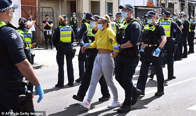 A woman was detained by police as hundreds flocked to Melbourne's CBD to demand restrictions be eased