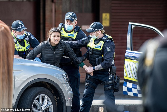 Victorian police officers arrest a female protester near the Queen Victoria Markets, during a popup anti-mask and anti lockdown protest at the market on Sunday